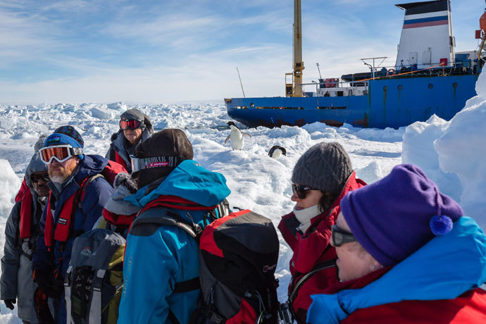 The first load of passengers from the stranded Russian ship MV Akademik Shokalskiy (back R) wait for a helicopter from the nearby Chinese icebreaker Xue Long to pick them up as rescue operations take place after over a week of being trapped in the ice off Antarctica. (AFP Photo / Andrew Peacock )