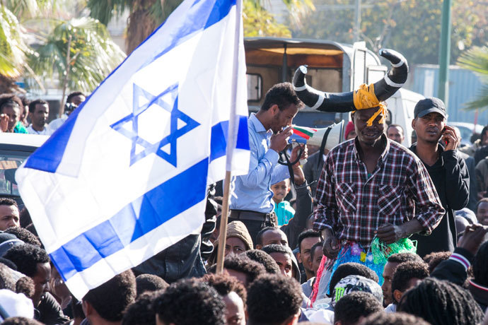 Protestors wave an Israeli flag as thousands of African asylum seekers demonstrate outside several Western embassies in the Mediterranean coastal city of Tel Aviv on January 6, 2014.(AFP Photo / Jack Guez)