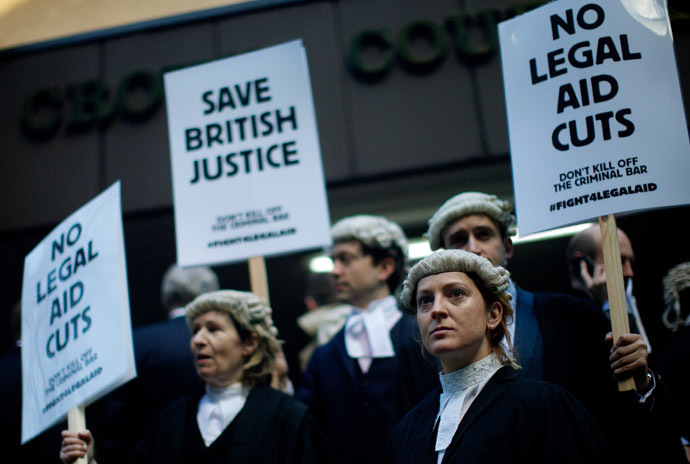 British legal professionals hold placards during a protest against cuts to the legal aid budget during a protest outside Southwark Crown Court in London on January 6, 2014 (AFP Photo/Andrew Cowie)