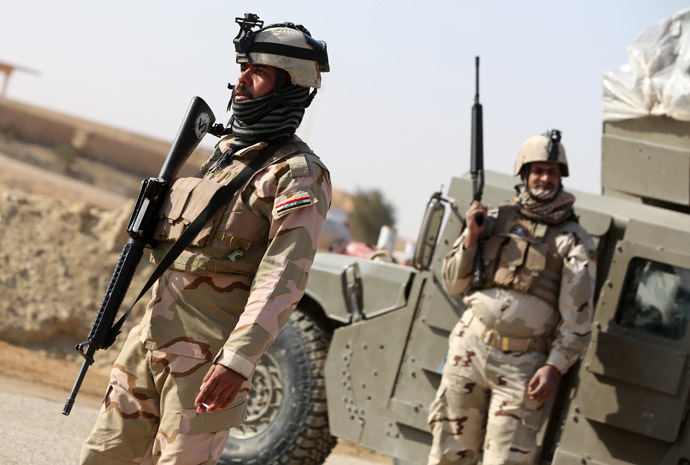 Iraqi soldiers stand along a road close to their vehicle in the area of Ein Tamer which leads west out of the central Iraqi Shiite Muslim shrine city of Karbala towards the mainly Sunni Muslim city of Fallujah, in the bordering Anbar province, on January 6, 2014. (AFP Photo)