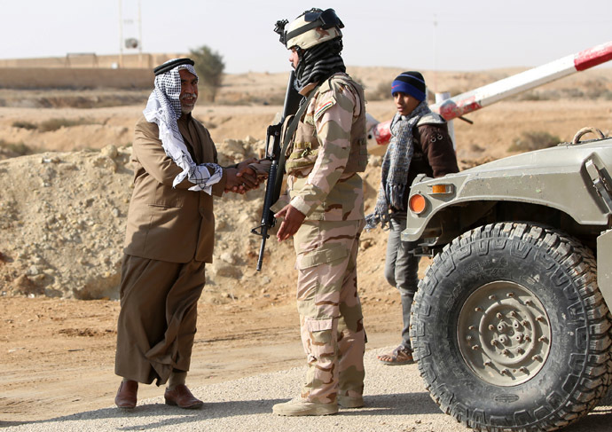 A Sunni Muslim Iraqi man shakes the hand of a soldier at Ein Tamer as families flee their homes in the city of Fallujah making their way to the central Iraqi Shiite Muslim shrine city of Karbala, on January 6, 2014. (AFP Photo)