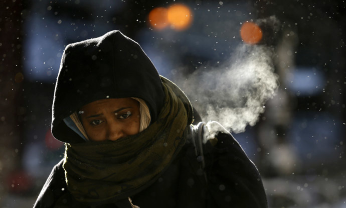A woman walks in frigid cold temperatures though downtown Chicago, Illinois, January 6, 2014. (Reuters/Jim Young)