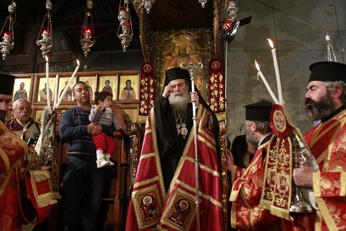 Greek Orthodox Patriarch of Jerusalem Theophilos III leads the service at the Church of the Nativity in the biblical West Bank town of Bethlehem as Orthodox Christmas celebrations kicked off on January 6, 2014, in the traditional birthplace of Jesus Christ. (AFP Photo / Musa Al-Shaer)