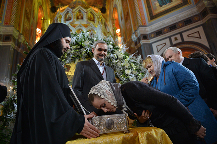 Parishioner kisses the chest containing a holy relic - the Gifts of the Magi, brought to Moscow for the first time from St. Paul's Monastery on Mount Athos, during the festive Christmas service at the Cathedral of Christ the Saviour. (RIA Novosti / Vladimir Astapkovich)
