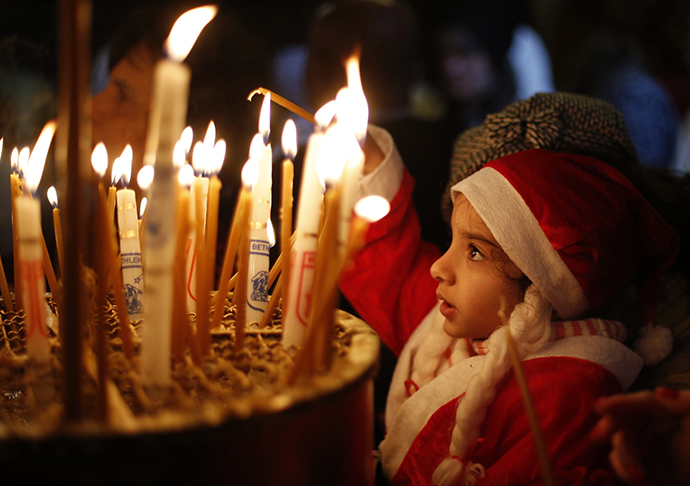 A child wearing a Santa Claus costume lights a candle inside the Church of the Nativity in the West Bank town of Bethlehem during the Eastern Orthodox Christmas January 6, 2014. (Reuters / Mohamad Torokman)