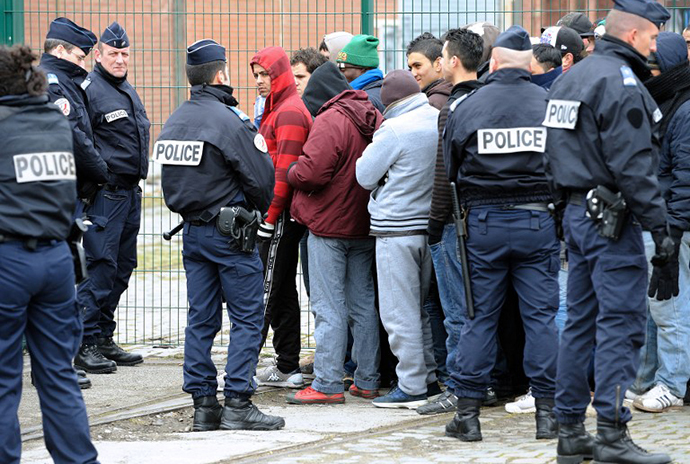 "French police watch illigal immigrants wait in line on February 28, 2013 to receive meals from the ""La Belle Etoile"" (Pretty Star) association in the port of the northwestern French city of Calais. (AFP Photo / Philippe Huguen)"