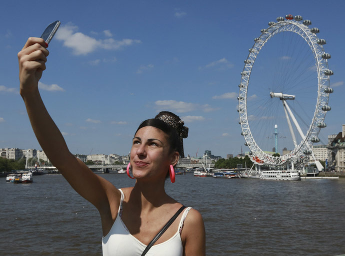 A tourist takes a picture of herself in front of the River Thames and the London Eye in central London (Reuters/Olivia Harris)