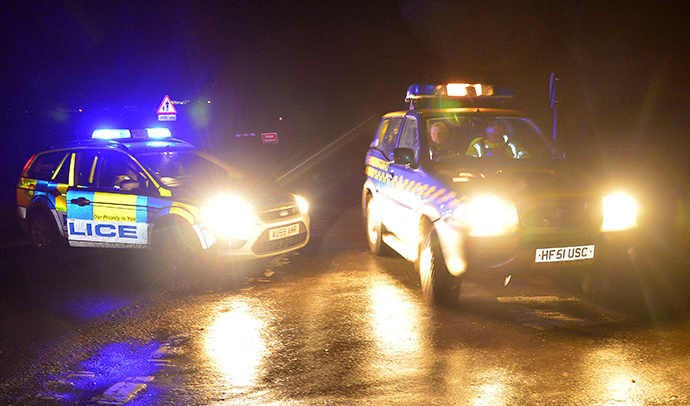 Emergency vehicles drive past a police road-block in the village of Cley in Norfolk, east England, January 8, 2014. (Reuters / Toby Melville)