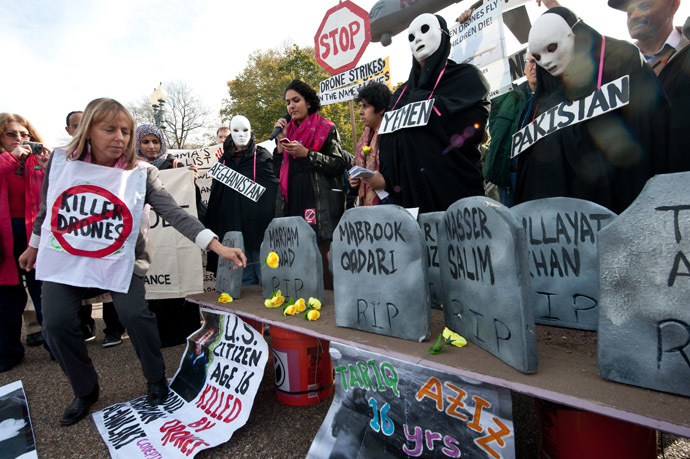 Medea Benjamin (L), co-founder of the anti-war group CodePink, places flowers on mock graves of drone victims in Afghanistan, Pakistan and Yemen, in front of the White House in Washington on November 15, 2013 ahead of the Global Drone Summit. (AFP Photo)