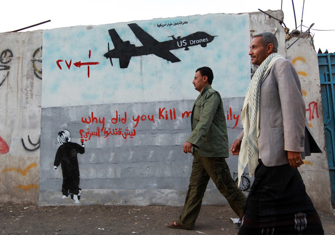 "Yemeni men walk past a mural depicting a US drone and reading "" Why did you kill my family"" on December 13, 2013 in the capital Sanaa. (AFP Photo)"
