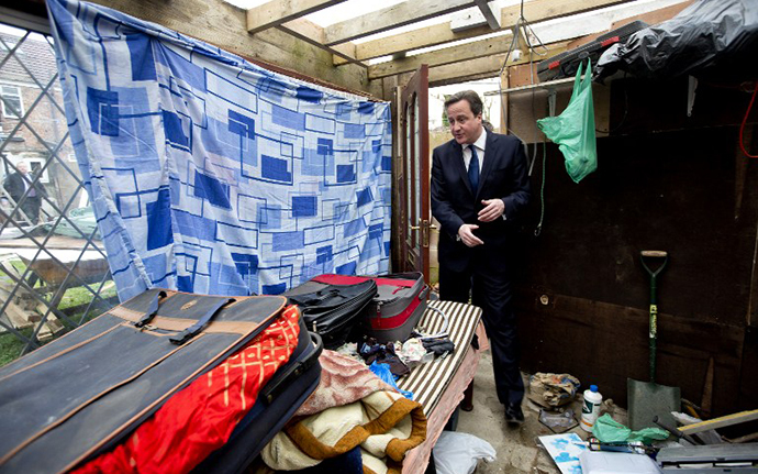 Britain's Prime Minister David Cameron is shown around a house in Southall in London on December 18, 2013 which was raided earlier in the day by immigration officers. (AFP Photo / David Bebber)