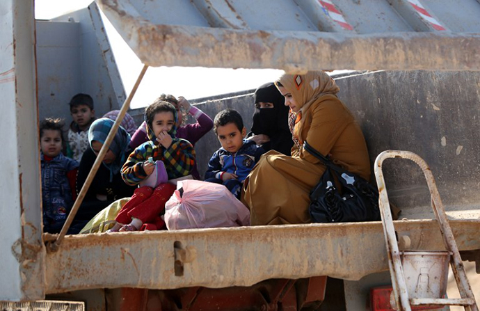 Iraqi women and children, who fled Fallujah, sit in the back of a truck as they wait at an army checkpoint at Ayn al-Tamer crossing at the entrance to Karbala province on January 6, 2014. (AFP Photo / Ahmad Al-Rubaye)