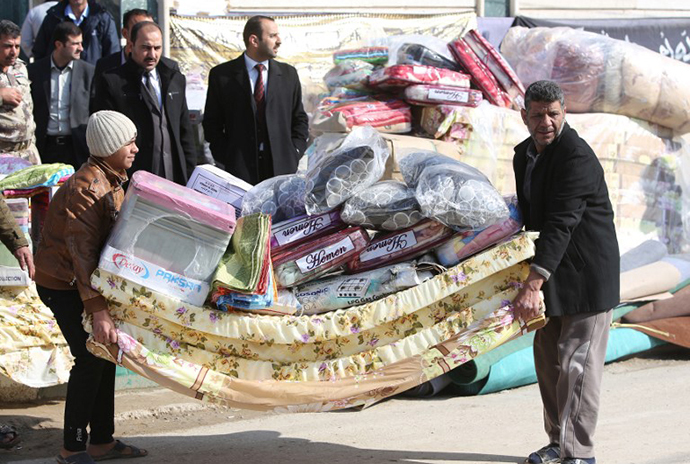 Sunni Muslim Iraqis who fled Fallujah with their families carry blankets and mattresses distributed by the International Organization for Migration (IOM) NGO on January 6, 2014 in Ayn al-Tamer in Karbala province. (AFP Photo / Ahmad Al-Rubaye)