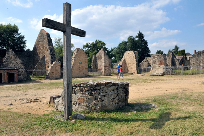 People visit on August 30, 2013 the martyr village of Oradour-sur-Glane, central France, where 642 citizens including 500 women and children were killed locked up in a church intentionally set on fire by a SS division on June 10, 1944. (AFP Photo / Thierry Zoccolan)