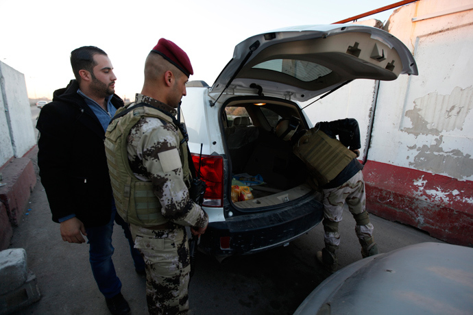 Iraqi soldiers check the trunk of a vehicle at a check point in west of Baghdad, January 8, 2014 (Reuters / Ahmed Saad)