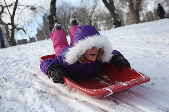 A young girl sleds down a hill in Central Park after a winter storm on January 3, 2014 in New York, United States. (AFP Photo / Getty Images / John Moore)