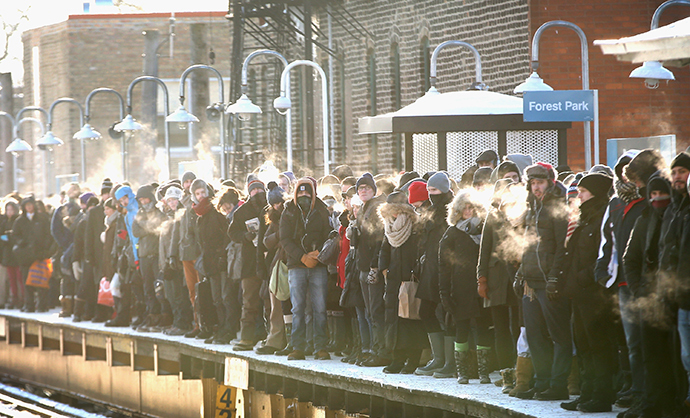 """Passengers heading into downtown wait on an """"L"""" platform for the train to arrive in below zero temperatures on January 7, 2014 in Chicago, Illinois. (AFP Photo / Getty Images / Scott Olson)"""