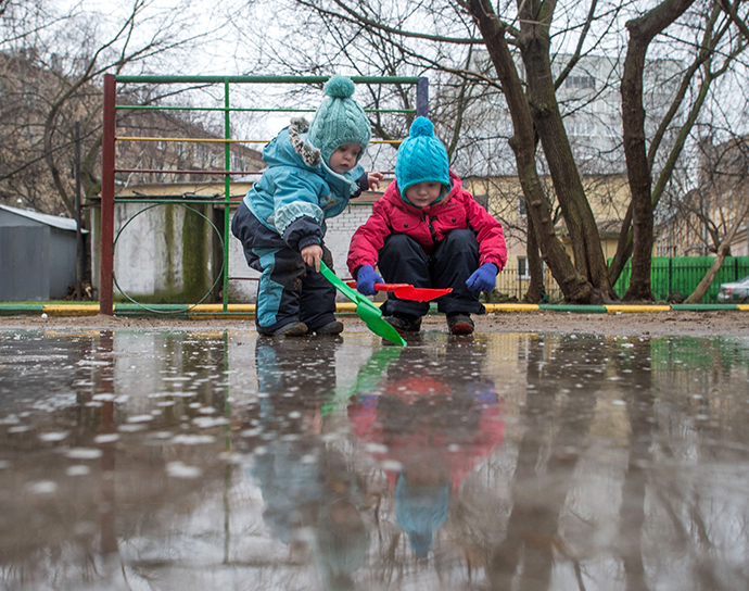 Children playing in a puddle in a courtyard on January 10, 2014. Abnormally warm weather has settled in Moscow. (RIA Novosti / Iliya Pitalev)