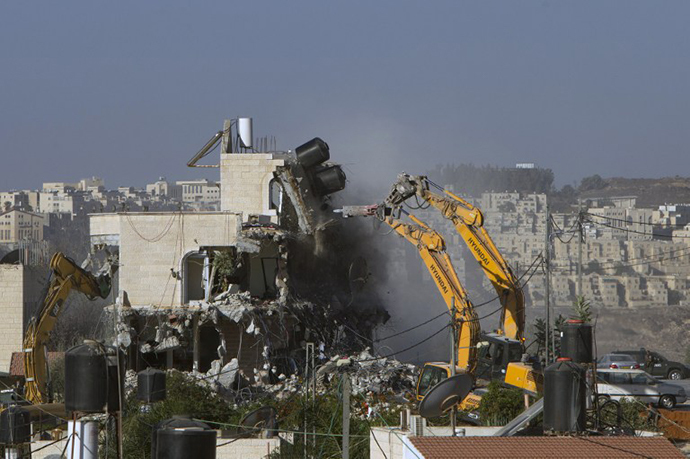 An Israeli municipality worker uses a mechanical shovel to demolish a house, belonging to a Palestinian family, that was built without municipal permission in the Arab east Jerusalem neighborhood of Beit Hanina on October 29, 2013. In the background is the Israeli settlement of Ramat (AFP Photo / Ahmad Gharabli)