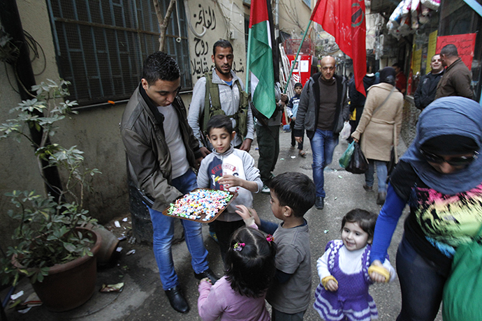 Palestinian refugees living in the the Shatila refugee camp in the Lebanese capital, had out sweets as they celebrate following the news of the death of former Israeli premier Ariel Sharon, on January 11, 2014. (AFP Photo / Anwar Amro)