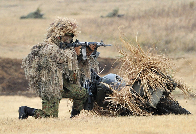 A camouflaged member of Japanese Ground Self Defense Forces' airbourne troops holds an automatic rifle during the new year exercise in Narashino in Chiba prefecture, suburban Tokyo on January 12, 2014 (AFP Photo / Yoshikazu Tsuno)