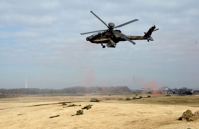 Japanese Ground Self Defense forces' AH-1 helicopter flies over military vehicles and personnels during the new year exercise in Narashino in Chiba prefecture, suburban Tokyo on January 12, 2014 (AFP Photo / Yoshikazu Tsuno)