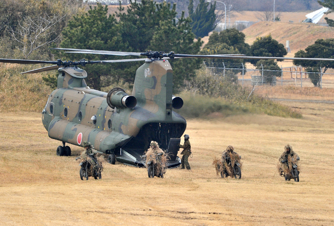 Japanese Ground Self Defense forces' airbourne troop personnel riding on their motorcycles run out from a CH-47 helicopter during the new year exercise in Narashino in Chiba prefecture, suburban Tokyo on January 12, 2014 (AFP Photo / Yoshikazu Tsuno)