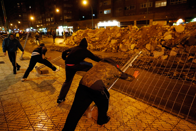 Demonstrators push down fencing in protest against imminent construction works to revamp Vitoria street, the city's main thorough-fare, in Burgos on January 12, 2014 (AFP Photo / Cesar Manso)