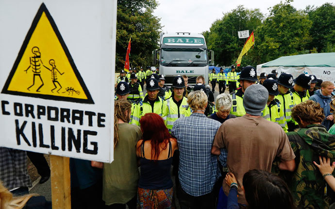 Demonstrators stand in the road as police escort a lorry to the entrance of a drilling site run by Cuadrilla Resources, in the village of Balcombe in southern England September 3, 2013.(Reuters / Luke MacGregor)