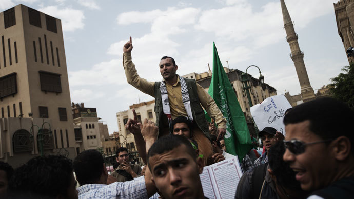 An Egyptian man shouts religious slogans near the green Hamas movement flag during a demonstration in support of the Palestinian people and of Muslims around the world, on May 10, 2013 front of the Al-Ahzar mosque in Cairo.(AFP Photo / Gianluigi Guercia)