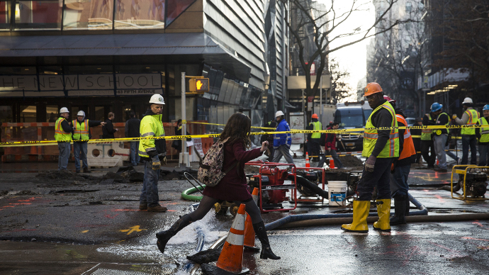 A woman jumps over water being pumped out of a hole in the street, caused by a water main break on January 15, 2014 in New York City. (AFP Photo / Andrew Burton)