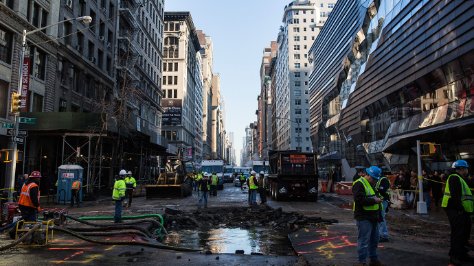 Workers monitor a hole caused by a water main break on 5th Ave and 13th St. on January 15, 2014 in New York City. (AFP Photo / Andrew Burton)
