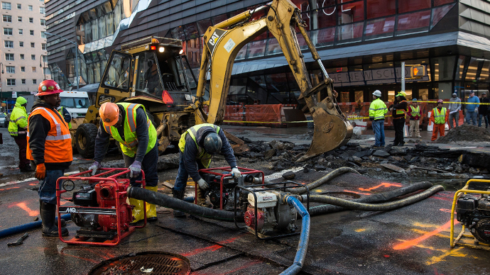 Workers use generators to pump water out of a hole in the street, caused by a water main break on 5th Ave and 13th St. on January 15, 2014 in New York City. (AFP Photo / Andrew Burton)
