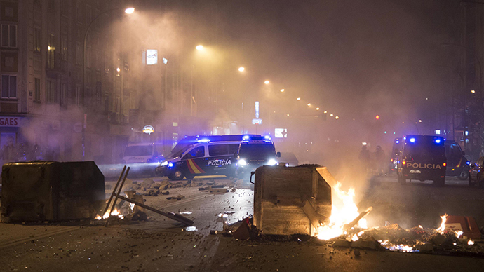 Garbage containers burn near Spanish National Police cars after demonstrators protested against construction plans of turning the main avenue Vitoria into a boulevard, in Burgos January 10, 2014. (Reuters / Ricardo Ordonez)