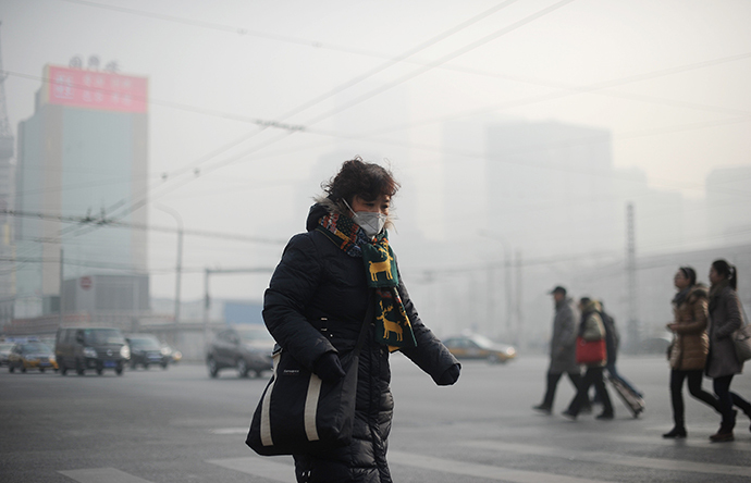 A woman wearing a face mask makes her way along a street in Beijing on January 16, 2014. (AFP Photo / Wang Zhao)