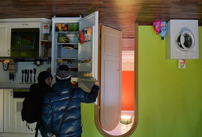 Visitors at the Upside Down House which opened at Moscow's All-Russian Exhibition Center. (RIA Novosti / Valeriy Melnikov)