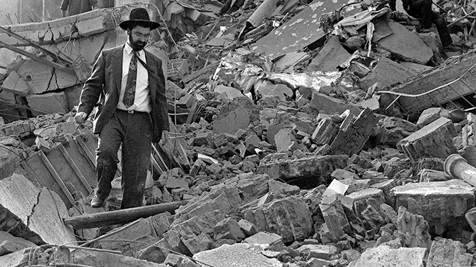 (FILE) A man walks over the rubble left after a bomb exploded at the Argentinian Israeli Mutual Association (AMIA in Spanish) in Buenos Aires, 18 July 1994. (AFP Photo / Ali Burafi)
