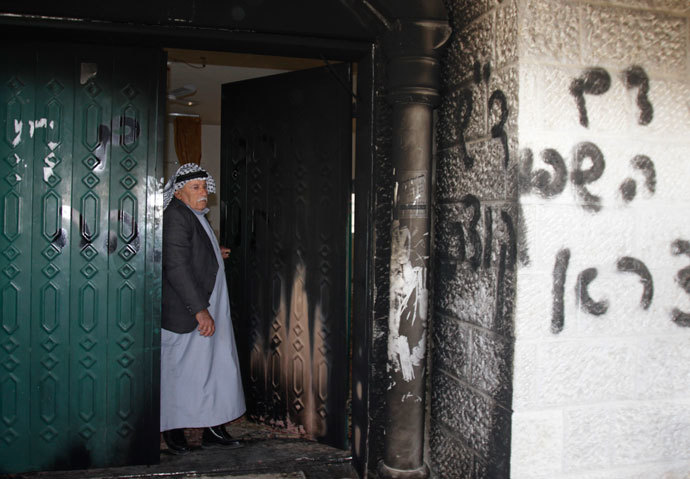 A Palestinian man stands near a door and wall of a mosque which were vandalised in the West Bank village of Deir Istiya, near the Jewish settlement of Ariel January 15, 2014.(Reuters / Abed Omar Qusini )