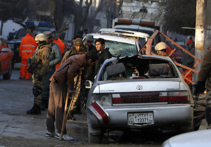 Fawad, a worker of a Lebanese restaurant who was injured during a suicide bombing attack outside the restaurant, looks at a damaged vehicle near the restaurant in Kabul January 18, 2014. (Reuters/Mohammad Ismail)