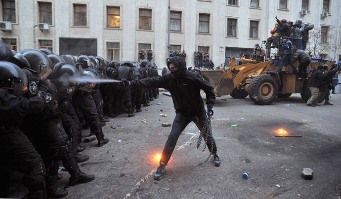 A protester uses tear gas against riot police during the storming of the Viktor Yanukovych Presidential office in Kiev during a mass rally of the opposition on December 1, 2013. (AFP Photo / Genya Savilov)