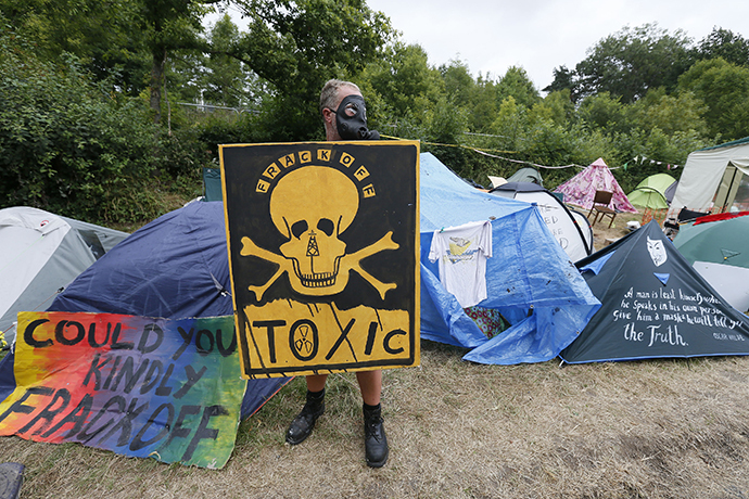 A demonstrator holds a placard at the protest camp, near the entrance to a site run by Cuadrilla Resources, near Balcombe in southern England August 16, 2013. (Reuters / Stefan Wermuth)
