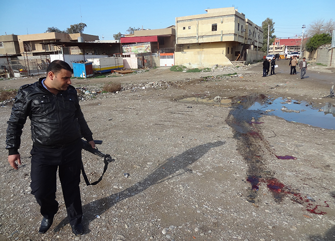 A member of Iraqi security forces inspects the site of a bomb explosion in the northern Iraqi city of Kirkuk on January 18, 2014. (AFP Photo / Marwan Ibrahim)