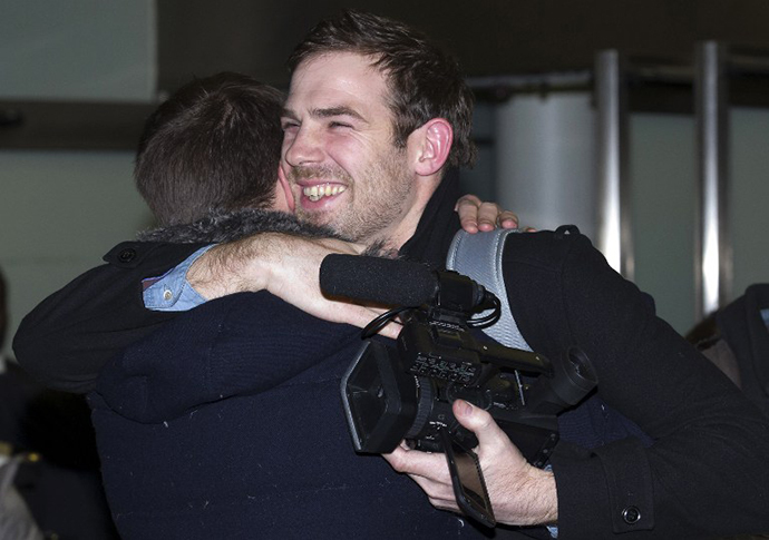 Journalist Kieron Bryan (R), who was detained in Russia with greenpeace activists, embraces his brother Russell at St Pancras International train station in London on December 27, 2013 after arriving back in Britain following an amnesty. (AFP Photo / Justin Tallis)