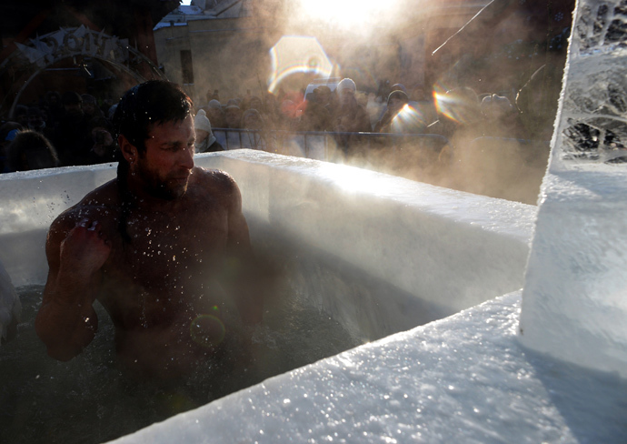 A Russian Orthodox man bathes in ice cold water near the Red Square in Moscow during a ceremony marking Epiphany on January 19, 2014. (AFP Photo / Vasily Maximov)