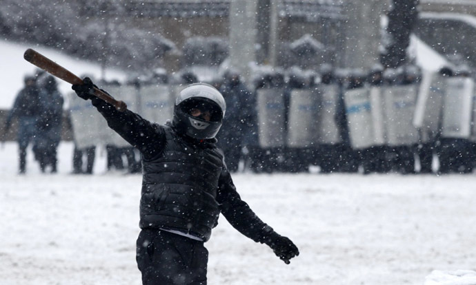 A pro-European protester gestures, with riot police officers seen in the background, during a rally in Kiev January 22, 2014. (Reuters/Vasily Fedosenko)