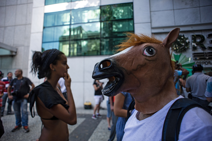 "A man wears a horse mask as he waits outside Leblon shopping mall, where a massive gathering called ""rolezinho"" was called, in Rio de Janeiro, Brazil on January 19, 2014 (AFP Photo / Yasuyshi Chiba)"