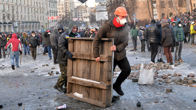 Protesters carry a wooden board to build barricades during clashes with the police in Kiev on January 20, 2014 (AFP Photo / Sergey Supinsky)