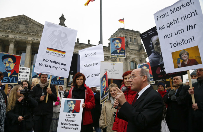 Gregor Gysy of the left-wing party Die Linke (R) addresses demonstrators supporting fugitive former U.S. National Security Agency contractor Edward Snowden, outside the Reichstag building, the seat of the German lower house of parliament Bundestag in Berlin November 18, 2013. (Reuters/Tobias Schwarz)