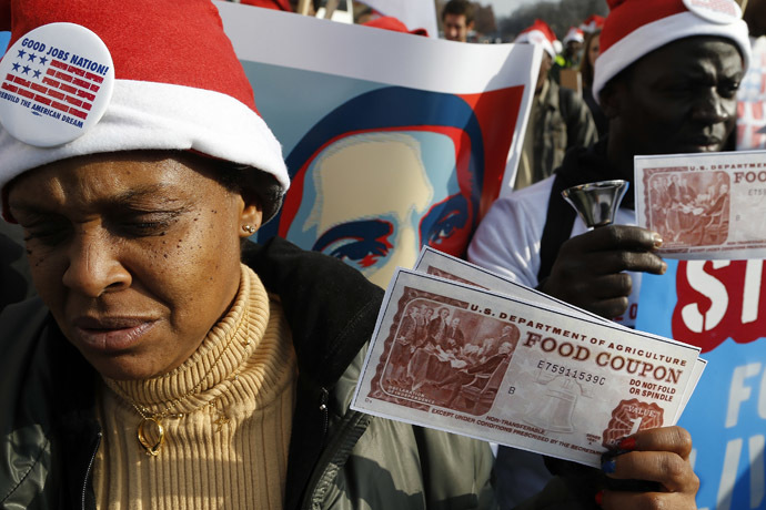 Protesters hold replicas of food stamps during a rally in support of higher pay for low-wage earners outside the National Air and Space Museum in Washington, December 5, 2013. (Reuters/Jonathan Ernst)