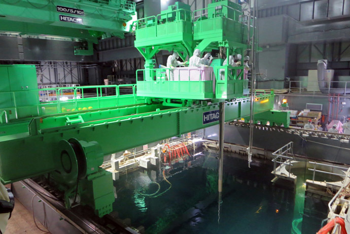 This handout picture taken by Tokyo Electric Power Co. (TEPCO) on November 26, 2013 shows TEPCO workers operating to move a spent fuel rod to a cask, in the storage pool as TEPCO transfers the fuel rods from crippled unit four reactor building to the pool at TEPCO's Fukushima Dai-ichi nuclear plant at Okuma town in Fukushima prefecture. (AFP/TEPCO)
